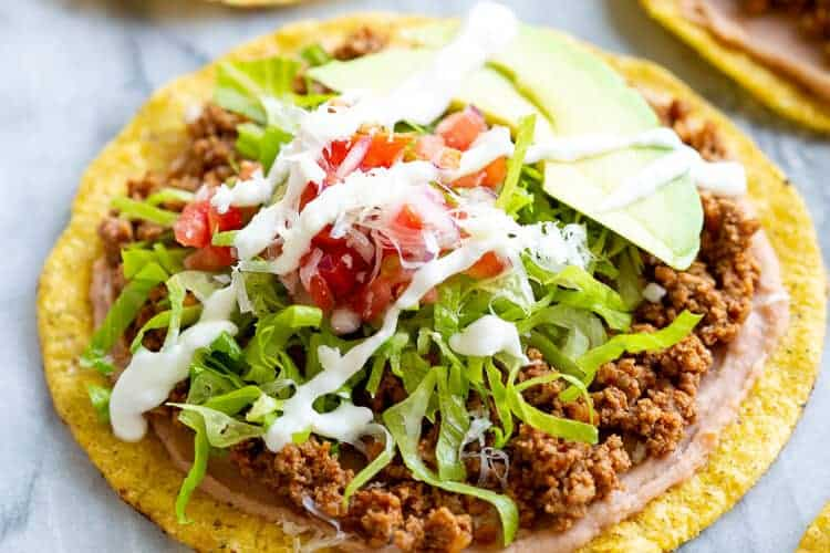 Tostada shells topped with refried beans, seasoned ground beef, lettuce, avocado, pico de gallo and sour cream.