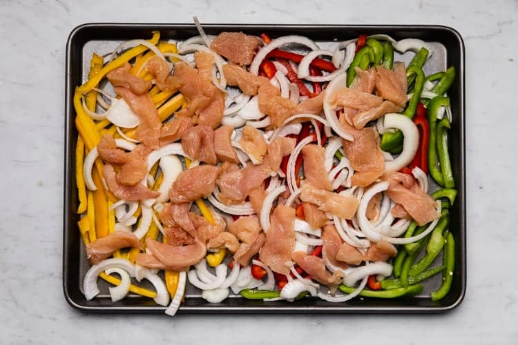 A sheet pan with chicken, bell pepper and onion sliced into strips.