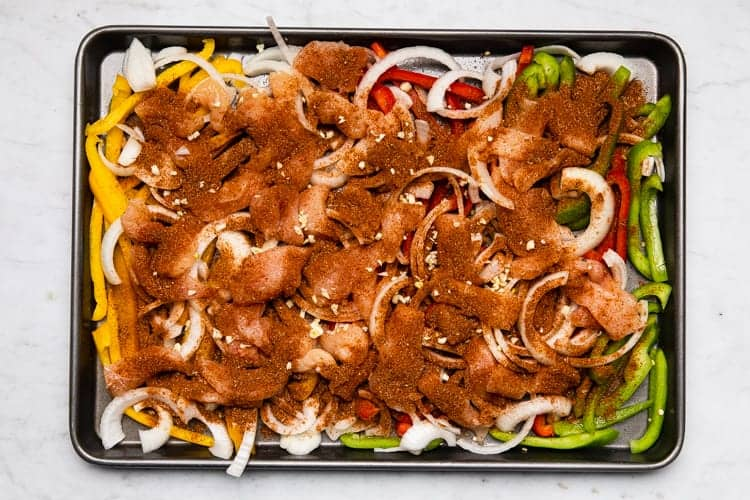 Fajita seasoning sprinkled over sliced chicken and vegetables on a pan.