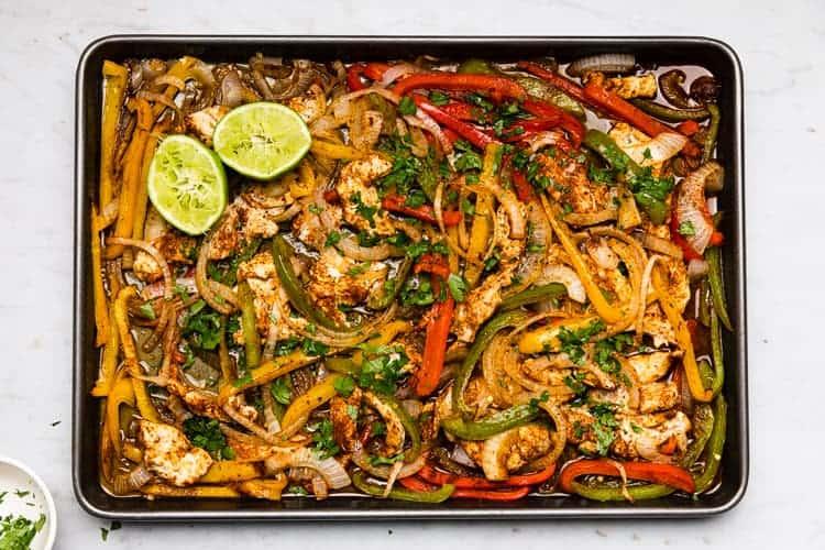Cooked sheet pan fajitas on a sheet pan.