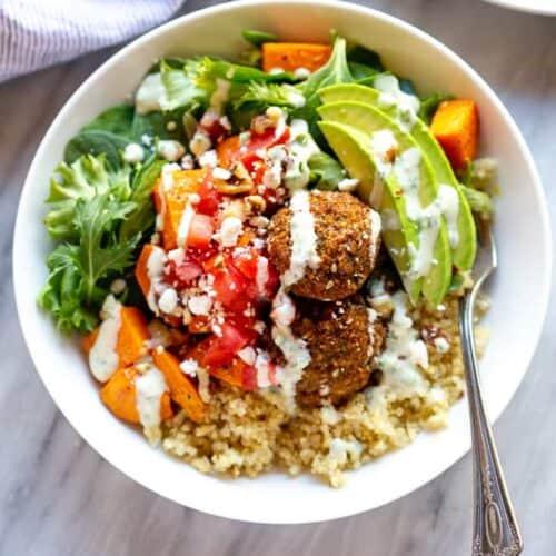 Buddha bowl with quinoa, veggies, falafel and white sauce.