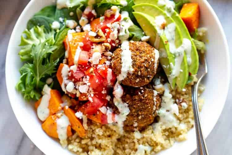 Buddha bowl with quinoa, veggies, falafel and white sauce.