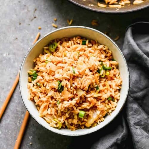 A bowl of kimchi fried rice with a skillet and chopsticks next to it.