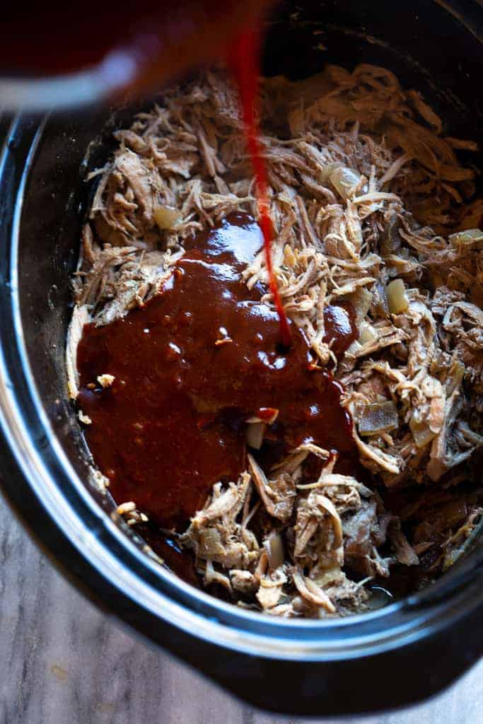 Red chili sauce poured over shredded pork in a slow cooker.