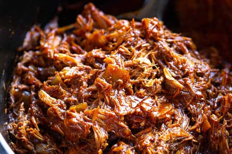 Shredded pork with red chili sauce in a slow cooker.