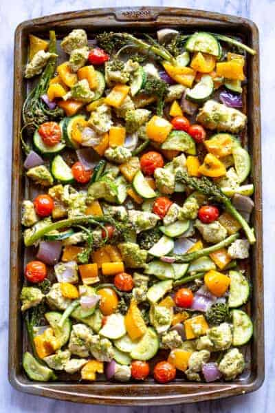 A sheet pan with pesto chicken and chopped vegetables.