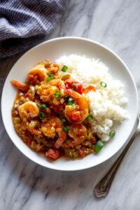 Shrimp creole on a plate with white rice.