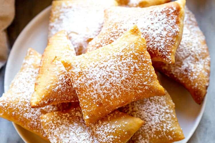 A plate full of sopapillas sprinkled with powdered sugar.