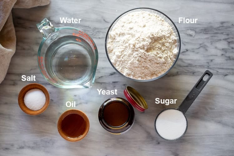 The ingredients needed to make bread including flour, sugar, yeast, water, oil and salt.