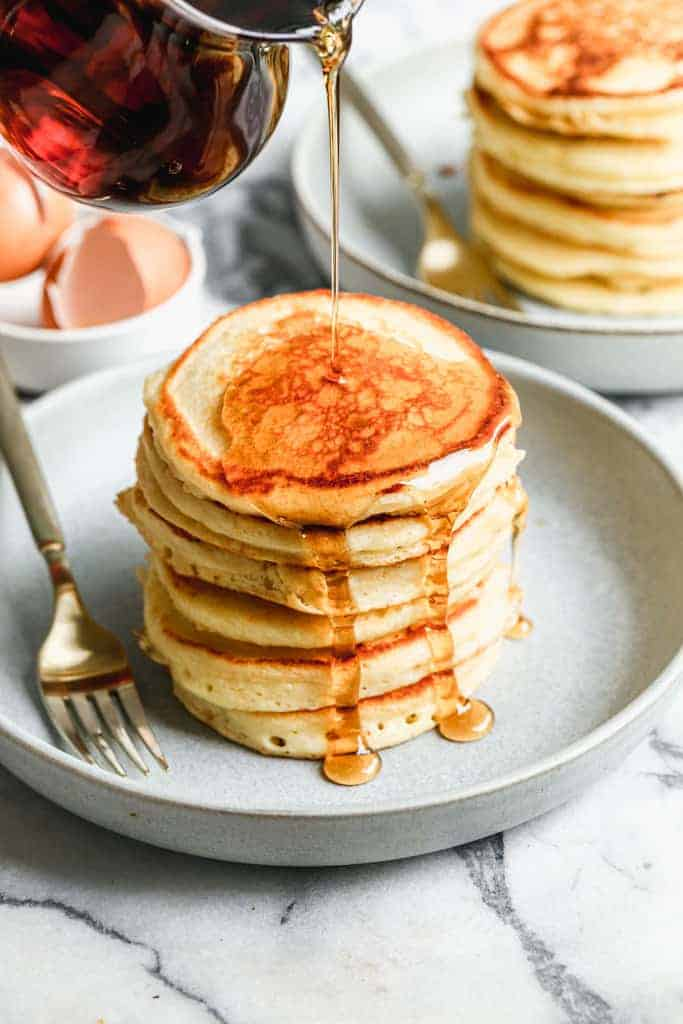 A large stack of buttermilk pancakes with syrup being poured over the top.