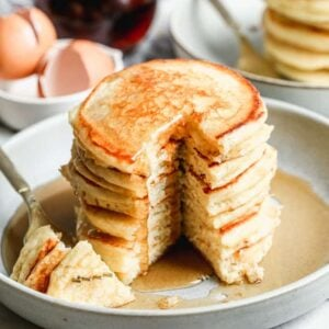 A stack of buttermilk pancakes with a big bite taken out by a fork.