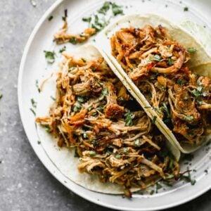 Two carnitas pork tacos on a plate.