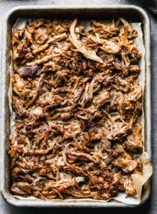 A sheet pan with crispy shredded pork carnitas.