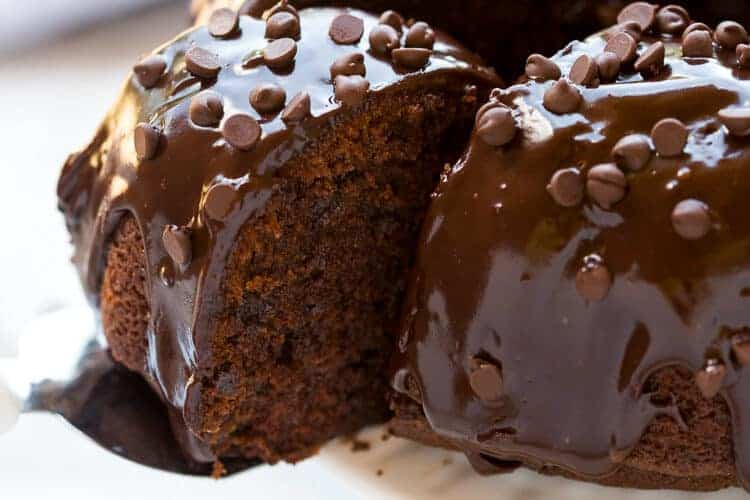 A slice of chocolate bundt cake being served from a cake stand with the whole cake on it.