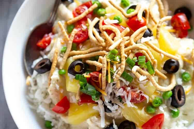 Hawaiian haystacks served over white rice, in a bowl with a spoon.