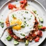 Homemade huevos rancheros on a plate with a fork.