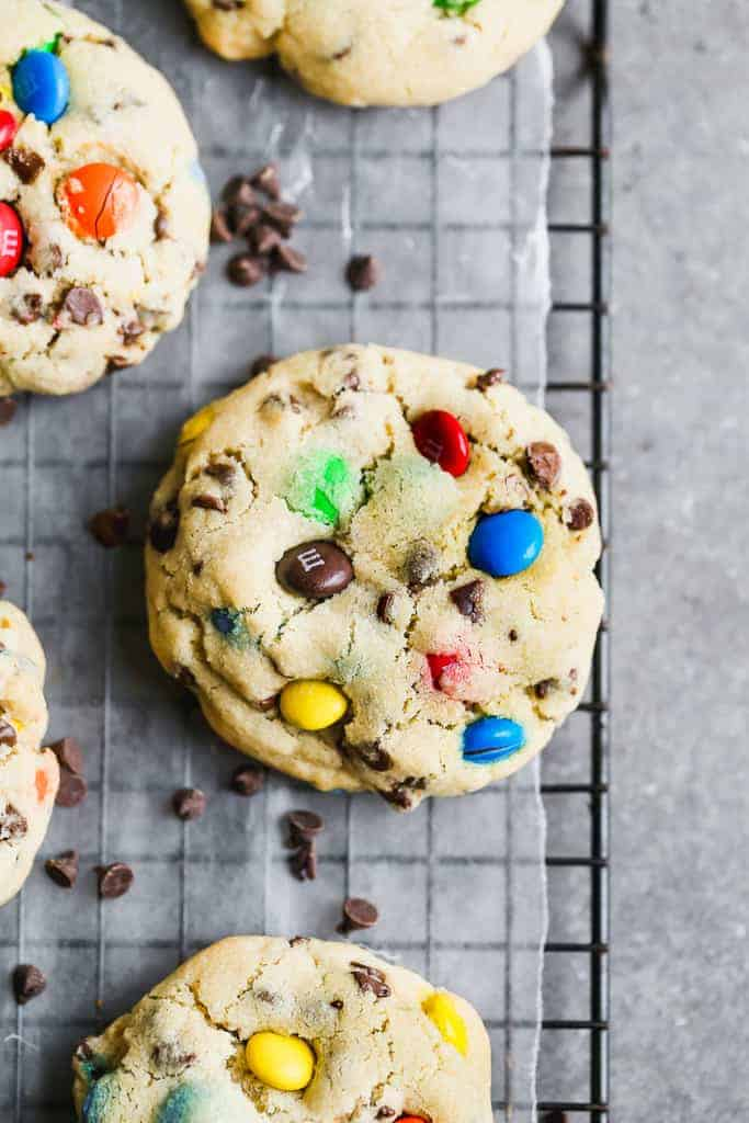 Large M&M cookies on a wore cooling rack.
