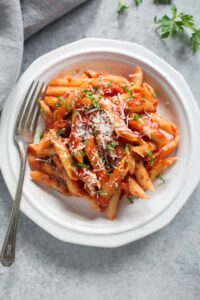 A white plate full of Italian penne arrabbiata.
