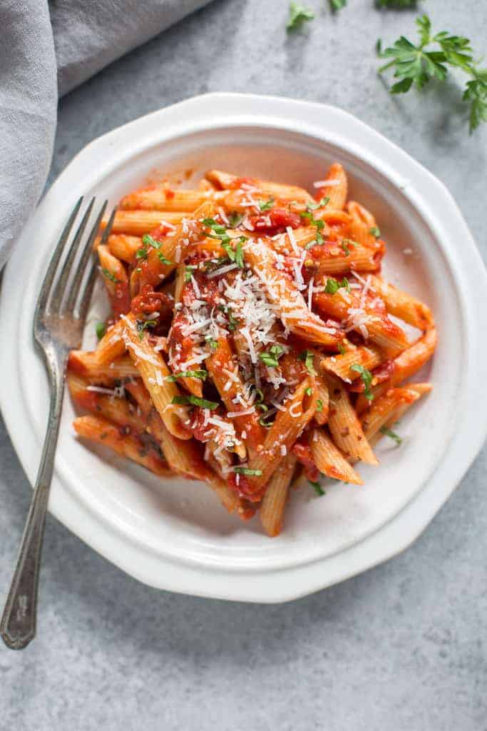 A white plate full of Italian penne arrabbiata garnished with fresh parmesan cheese.