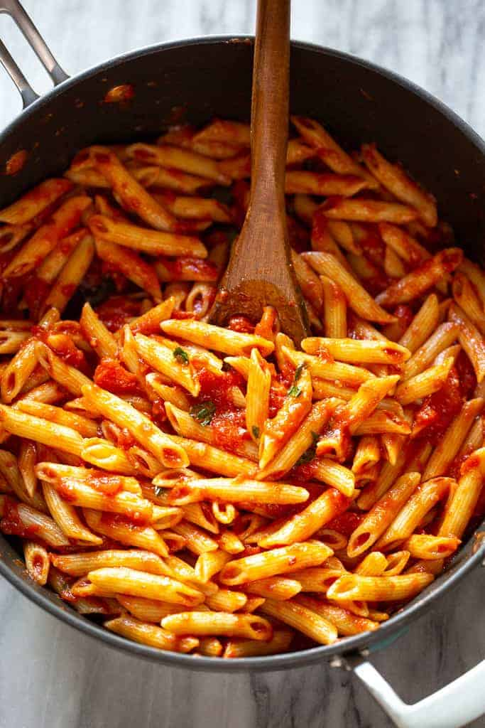 Penne pasta tossed in arrabbiata sauce in a skillet.