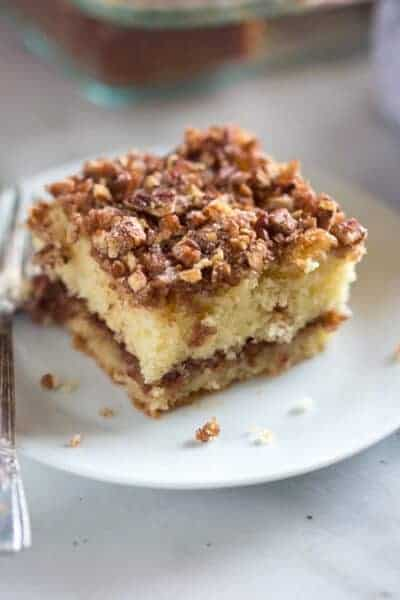 A slice of sour cream coffee cake on a plate with a fork.