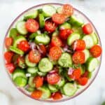 A bowl with chopped tomato, cucumber, onion and basil to make tomato cucumber salad.