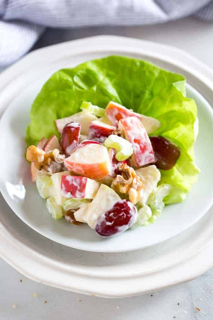 A lettuce leaf with Waldorf salad on it, on a plate.