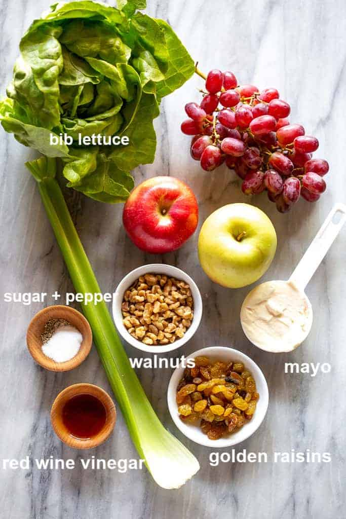 Labeled ingredients for Waldorf salad on a marble board.