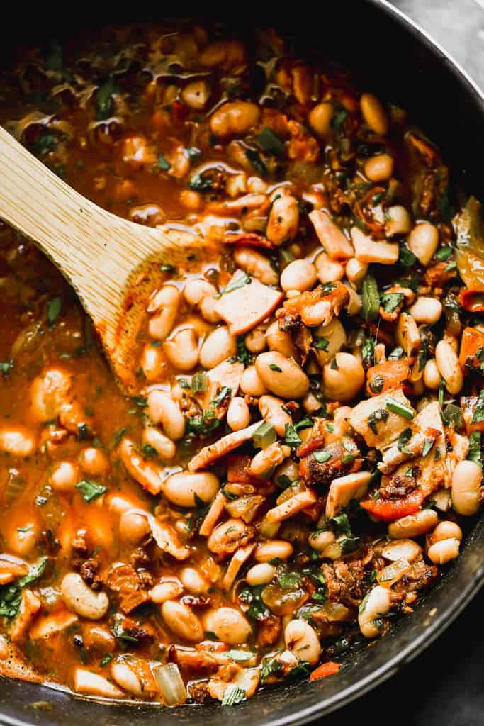 A pot of borracho beans with a wooden spoon in it for serving.