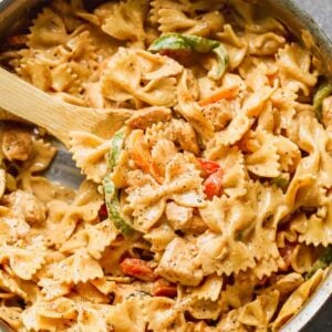 Cajun Chicken Pasta in a large skillet with a wooden spoon.