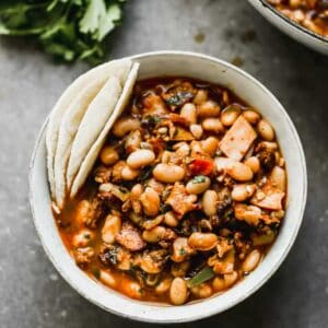 Charro beans served in a bowl with tortillas on the side.
