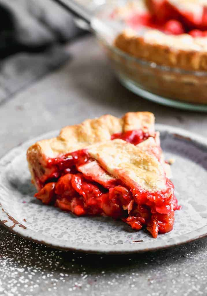 A slice of cherry pie on a plate.