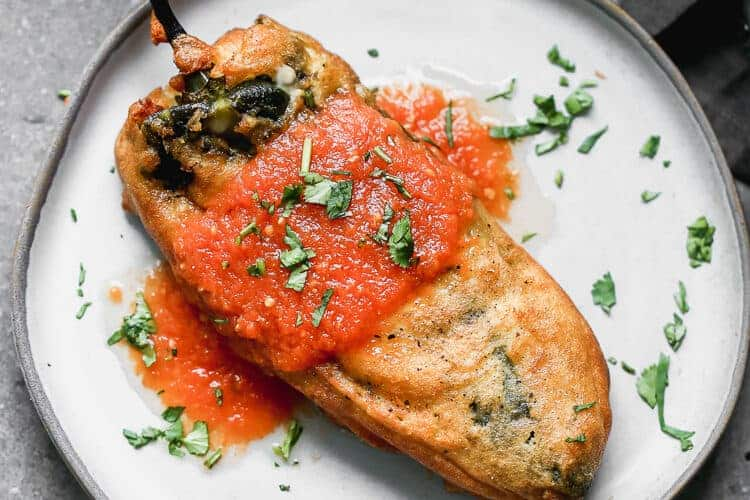 A plate with chile relleno topped with salsa roja.