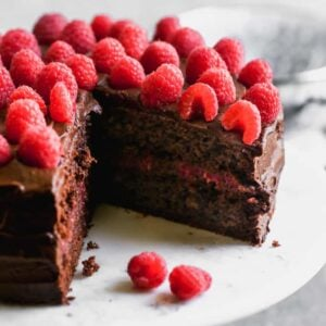 A two layer chocolate cake with raspberry filling and chocolate frosting and fresh raspberries on top.g