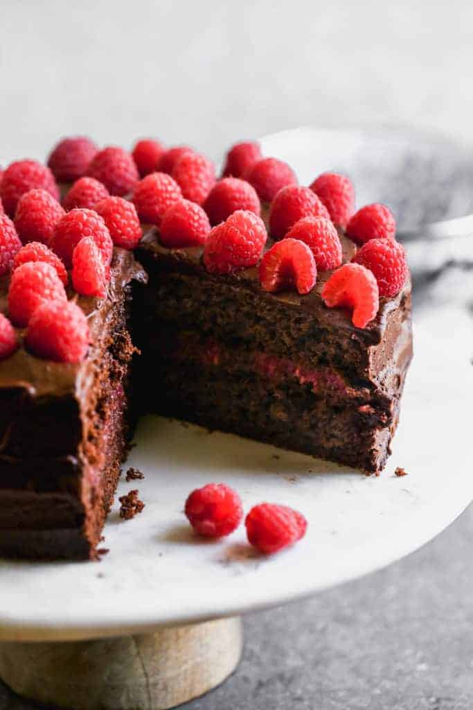 A two layer chocolate cake with chocolate frosting, raspberry filling and fresh raspberries on top.
