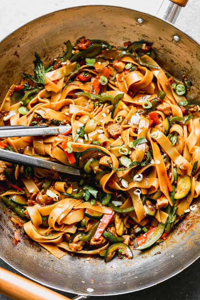 Tongs tossing Thai Drunken Noodles in a wok.