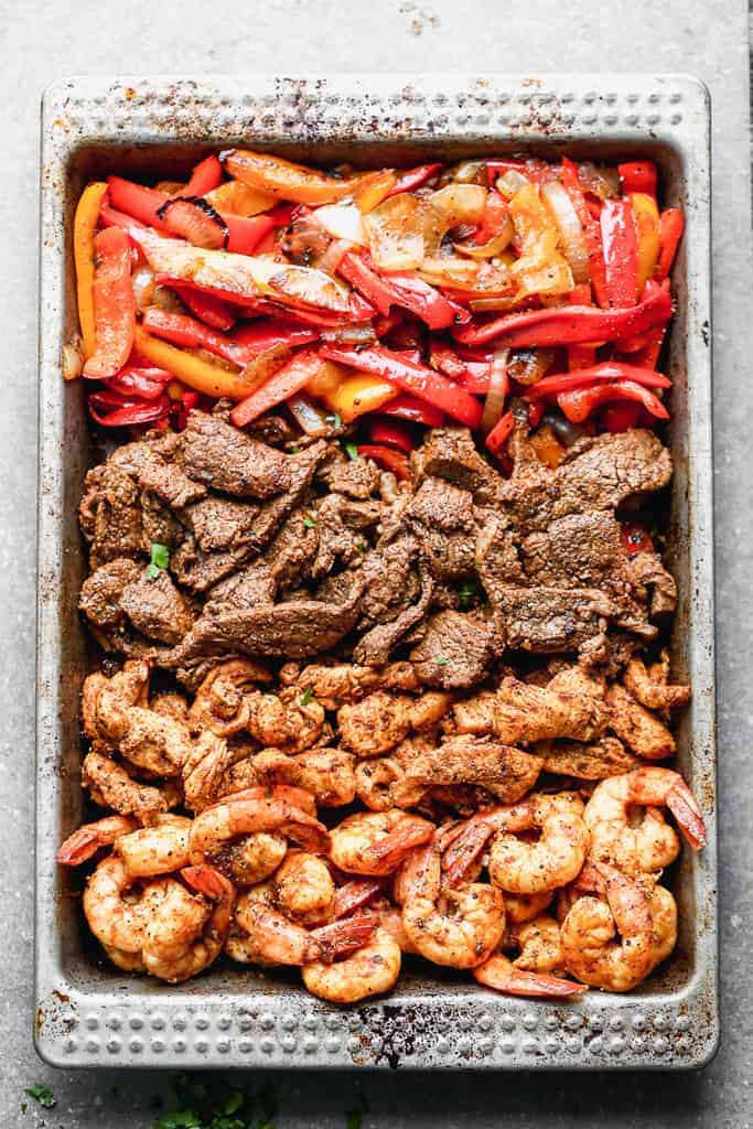 A sheet pan with meat and vegetables for fajitas including shrimp, chicken, steak, bell peppers and onion.