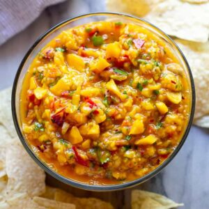 Mango Salsa served in a bowl surrounded by tortilla chips.