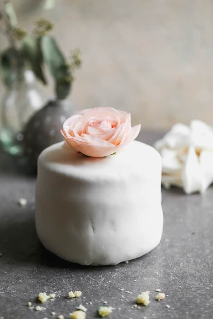 A small cake covered with white marshmallow fondant and a flower on top.
