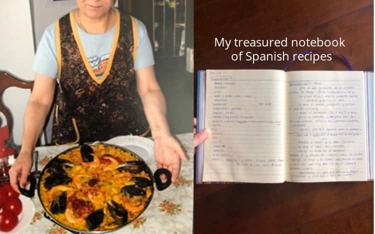 A Madrileña holding a pan of paella, next to a notebook with the a paella recipe written in Spanish.