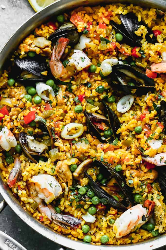 Close up of cooked chicken and seafood paella in pan, ready to eat.