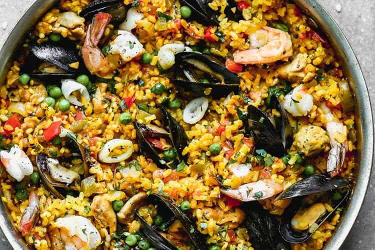 A large skillet full of chicken and seafood Paella.