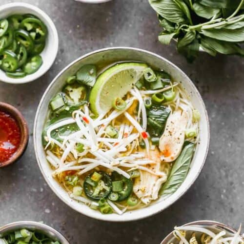 A bowl of Pho soup with chicken, cilantro, onion, basil, bean sprouts and a lime wedge.