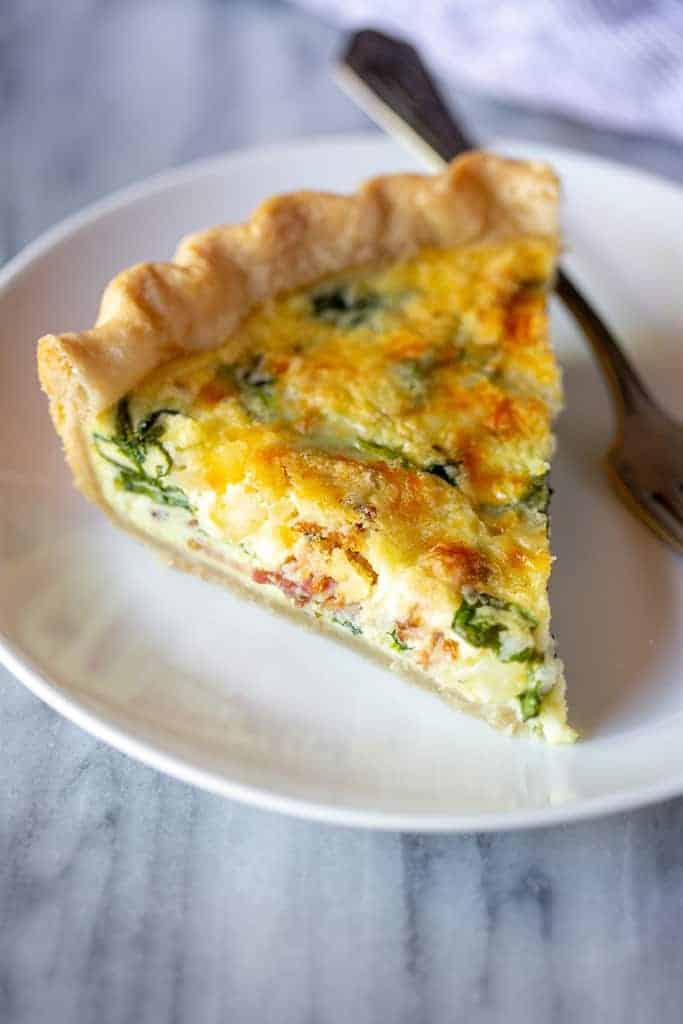 A slice of spinach and bacon quiche on a plate with a fork.