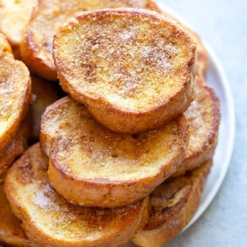 A stack of Torrijas on a white plate.