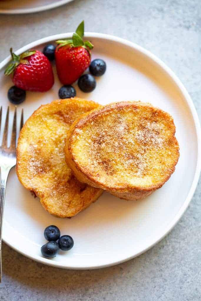 Two torrijas sprinkled with cinnamon sugar, on a plate with berries.