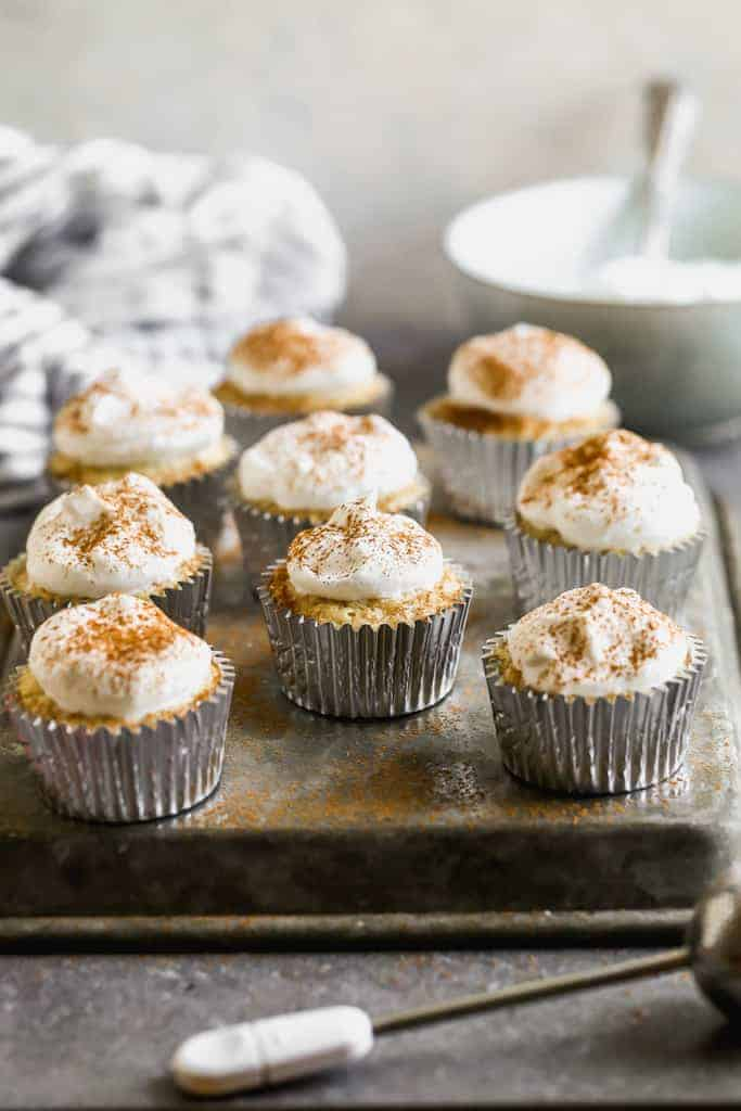 Tres Leches cupcakes topped with whipped cream and cinnamon, lined up on a baking tray.