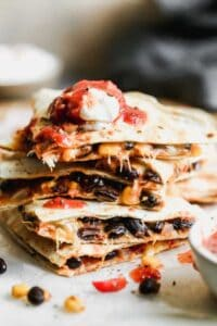 A stack of cut black bean quesadillas with salsa and sour cream on top.