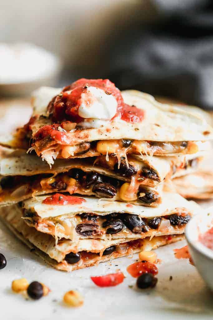 Une pile de quesadillas de haricots noirs coupés avec de la salsa et de la crème sure sur le dessus.