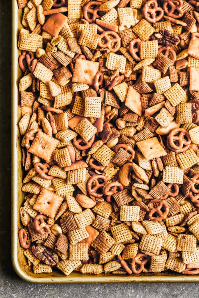 A baking sheet with seasoned, baked Chex mix.